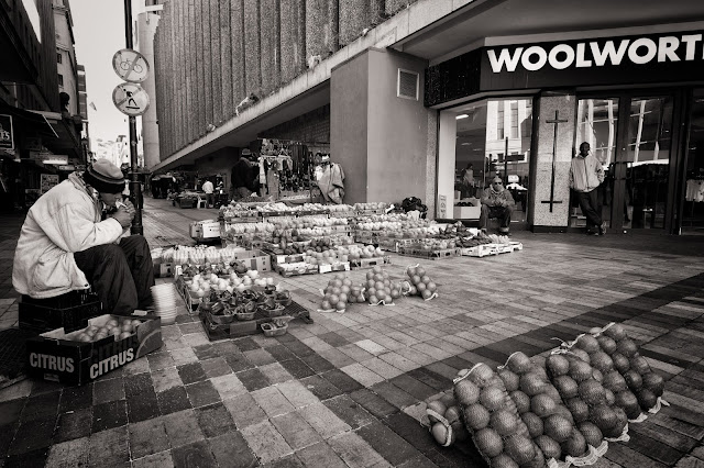A fruit and veg vendor lights a cigarette with his wares spread out in front of him