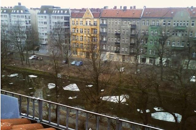 Von einer Dachetage aus fotografierte Häuserreihe, zu deren Füßen auf dem Kanal dicke, in Form und Größe unterschiedliche Schollen treiben.