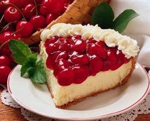 Platillo con porción de torta o pastel, hojitas de menta y canasta con cerezas