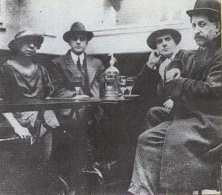The Dome was a cafe in Montparnasse much. Frequented by Modigliani, here seen in relaxed pose with his elbow on the table during a discussion with the part-time picture dealer, Adolphe Basler.