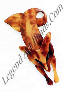 This stylized fox brooch is probably the most famous, and the most recognizable, of Lea Stein jewelry. The clever use of perspective and the swooping tail appear to make the fox jump right out at you. The assembly of various celluloid sheets forming a laminate pile, baking, cutting, and stenciling produce the variations in hues and detailing of inlaid eyes.