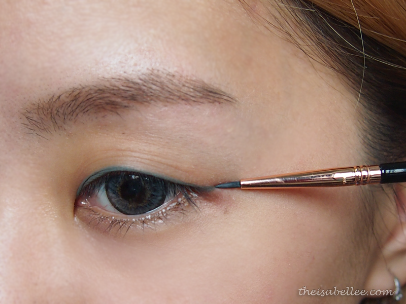Apply eyeliner using Sigma Beauty E11 Eye Liner