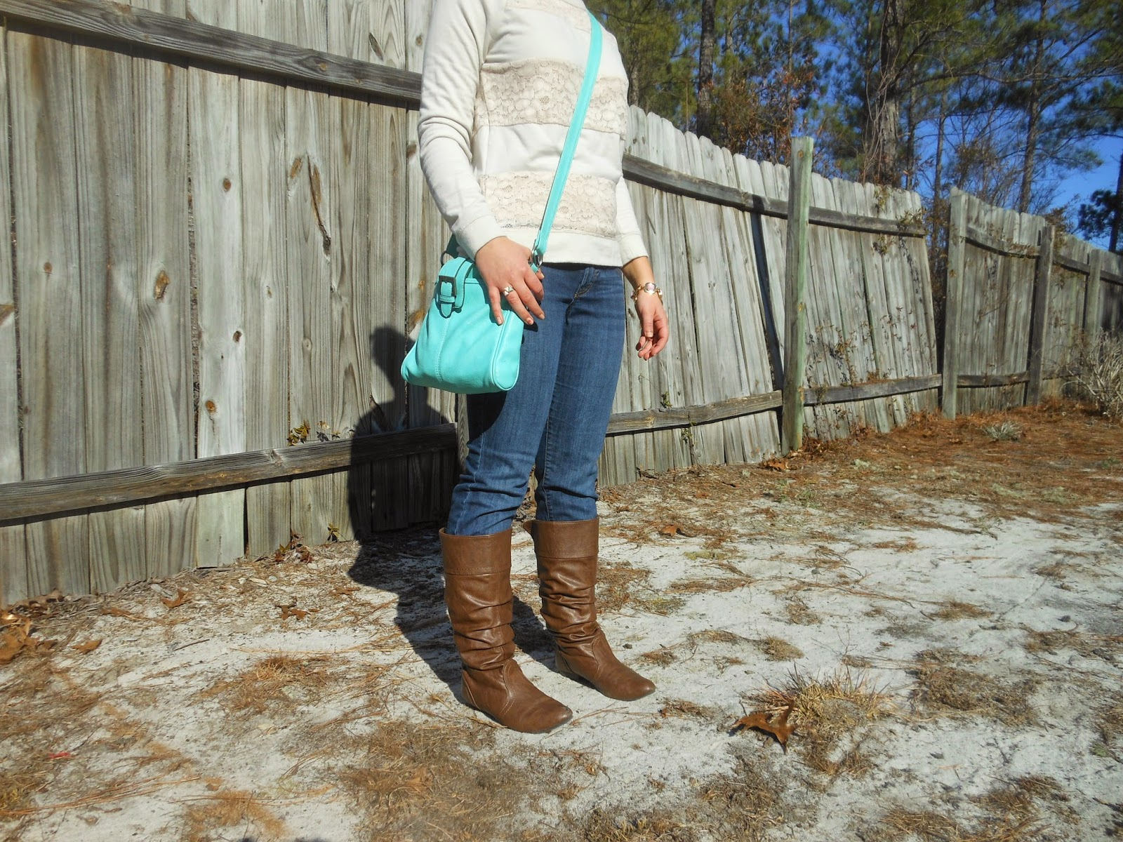 Brights for Winter. Lace sweatshirt, jeans, simple bright jewelry, bright blue purse, riding boots.