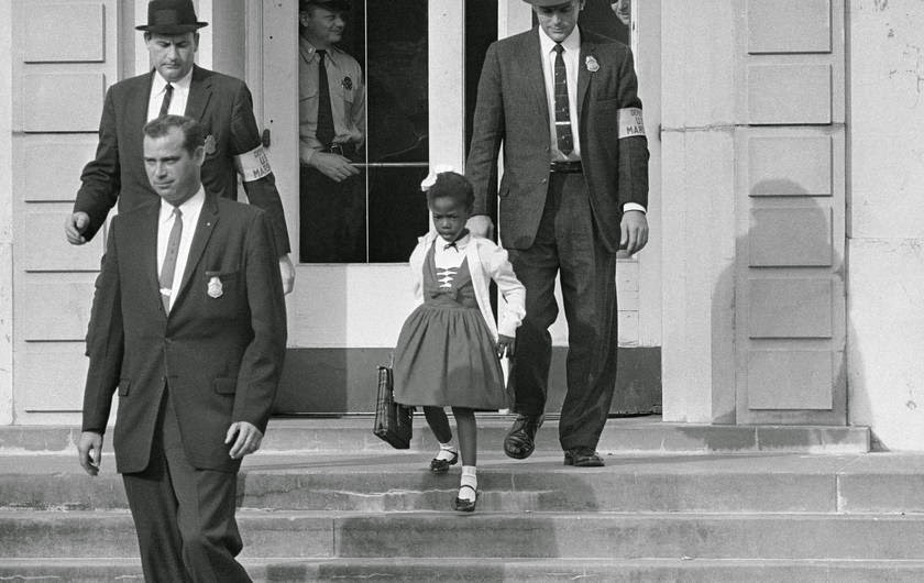 Photo of Ruby Bridges, age 6, walking down the steps of a white school, surrounded by federal marshals