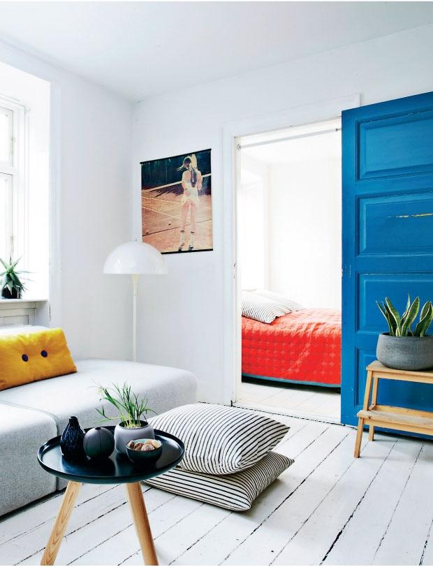hvide gulve, kunst og en blå dør som kontrast i dette skandinaviske hjem