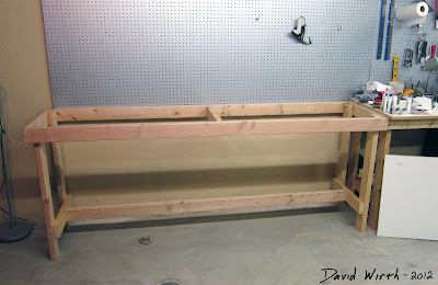 wood 2x4s bench and peg board on wall to hold tools