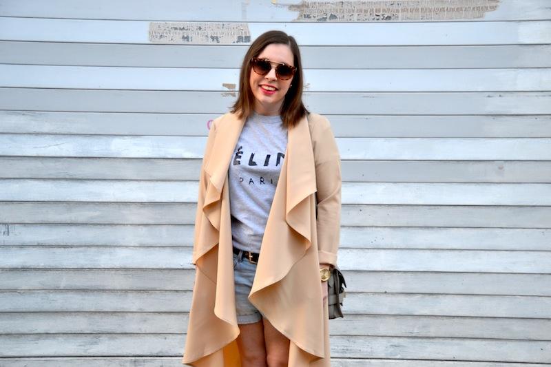 trench asymétrique long beige, top céline gris et short en jean et lunette de soleil écaille de l'usine à lunettes et sac like PS11