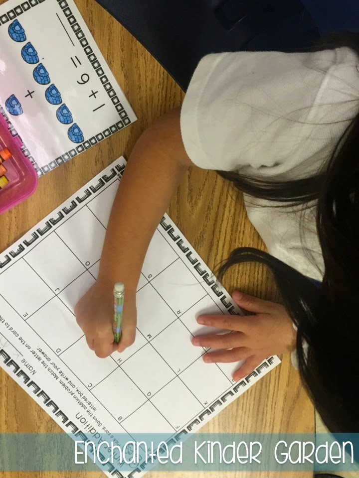 This is a photograph of a student writing on a task card recording sheet.