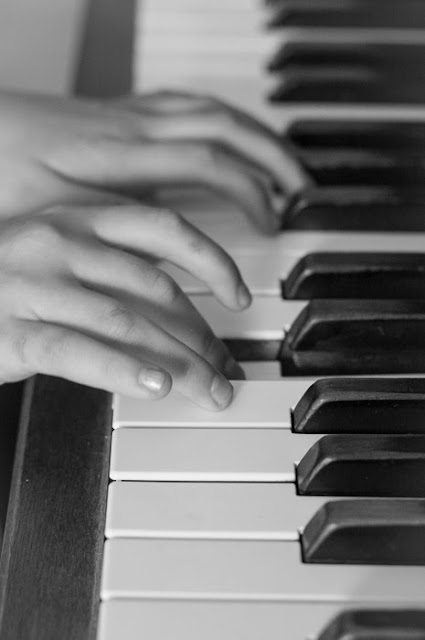 close-up of child's hands playing the piano