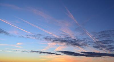 Foto: blauer Himmel mit rosa schimmernden Wolkenfetzen
