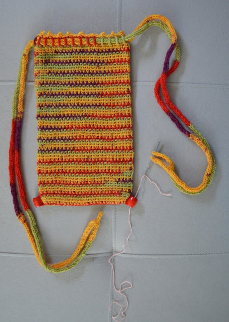 Rectangular crocheted drawstring bag laid flat with a bead stitched to each bottom corner.