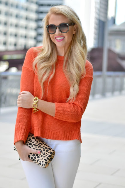 orange sweater with white jeans and leopard clutch