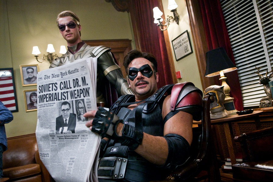 Watchmen 2009 holding newspaper with headline about Soviets calling Dr. Manhattan an Imperialist weapon movieloversreviews.blogspot.com