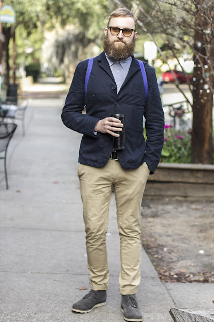 Dean Sidaway, SCAD Fashion Design Faculty, wears a three button navy blazer over a lighter blue shirt and rolled-up khaki pants  and gray suede boots.