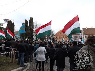Szöveg: ...lovukat peckesen megülő huszárokat és válogatott cigánylegényeket... Kép: Emberek sorfala között óriási magyar és székely zászlót lobogtatva vonul be egy sor fiatal egyes sorban.