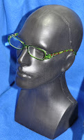 photo of green reader glasses on a black plastic head