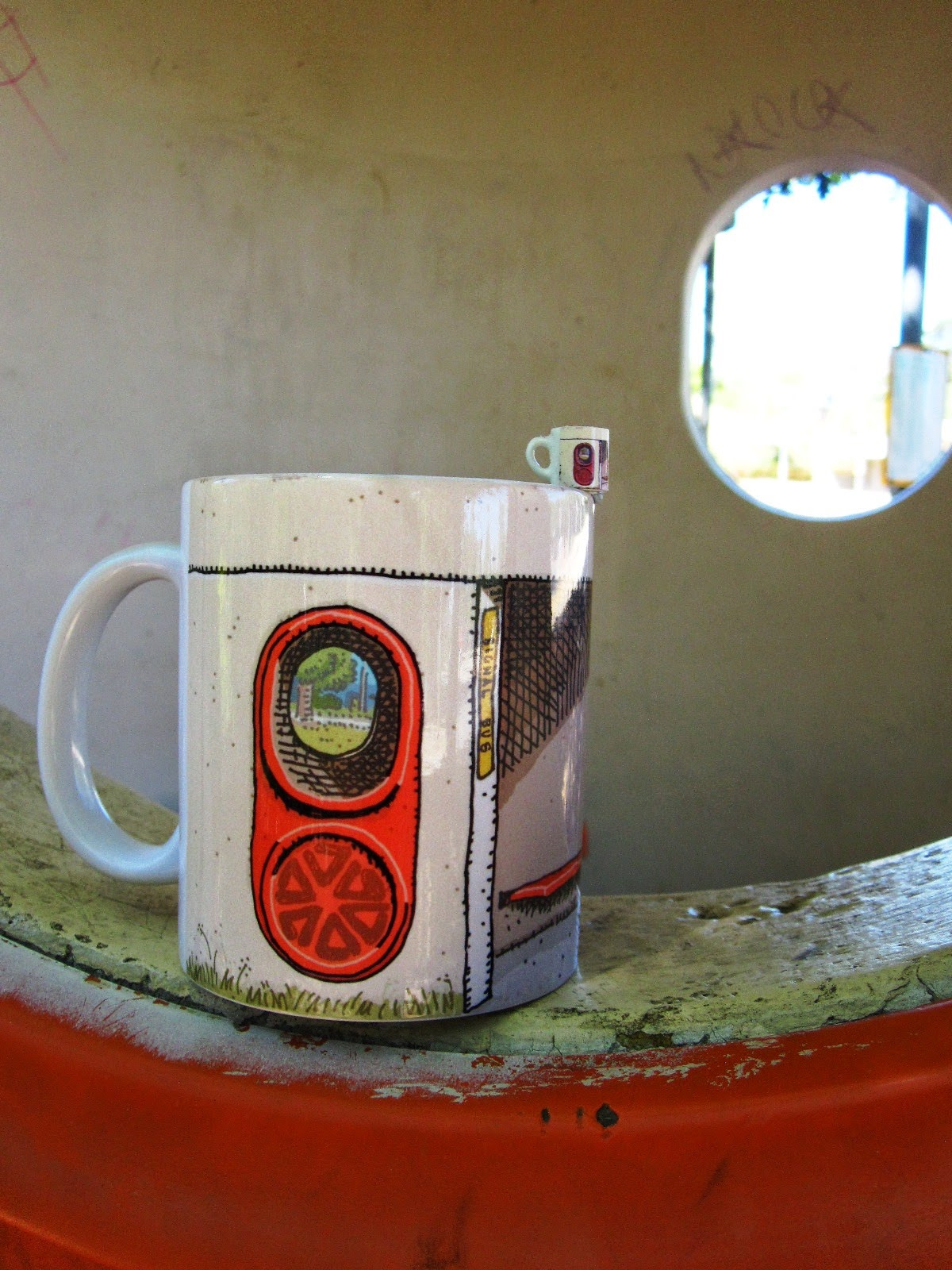 Dolls' house miniature mug with a Canberra bus shelter print, balanced on the edge of a full-sized Canberra bus shelter mug, sitting on the window ledge of a Canberra bus shelter.