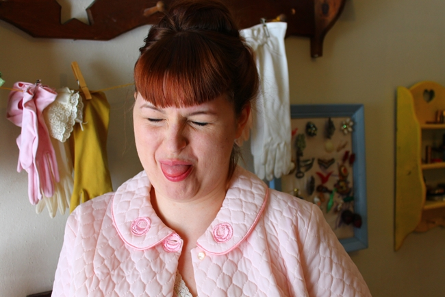 Brittany with new bags, making a silly face in pink vintage bed jacket