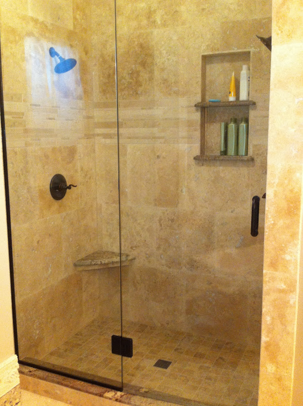 Travertine shower with two heads, marble accent tiles at eye level and  title=