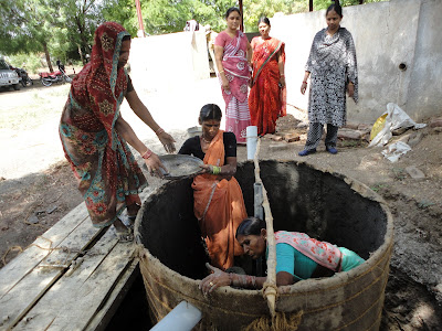 Women masons installing the floating dome FRP Biogas unit