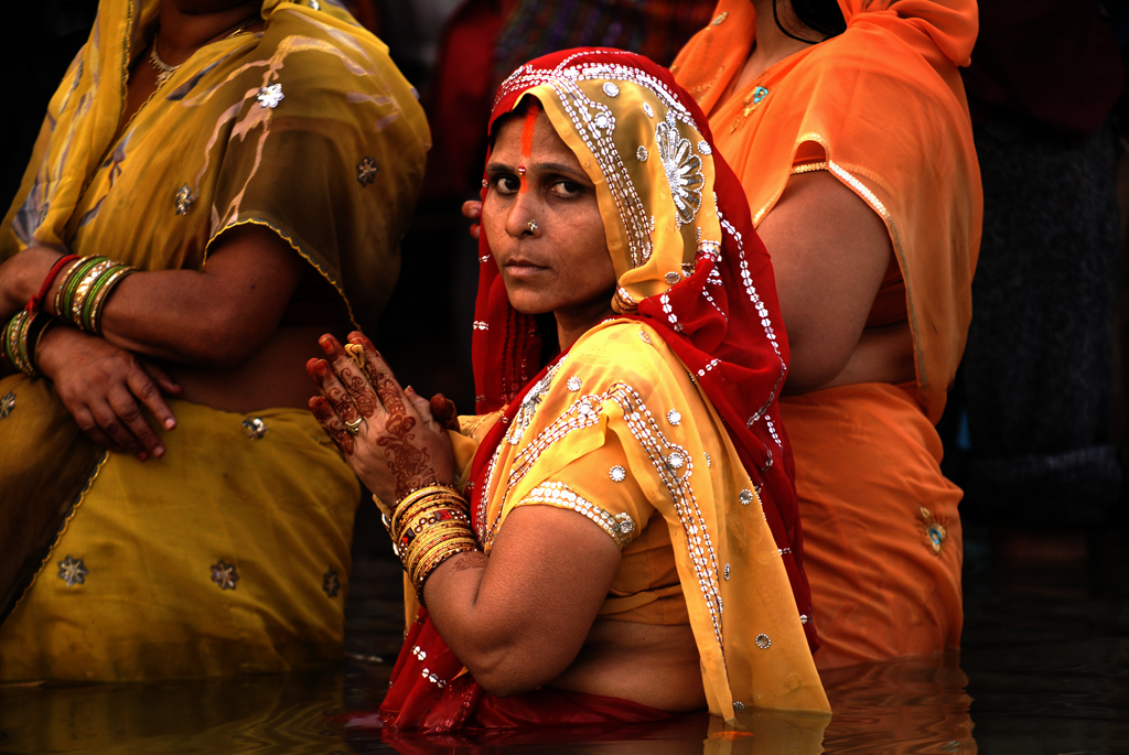 This is a photo of an Indian woman bathing in the Ganges River in Varanasi, India.