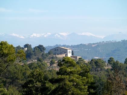 El mas de L'Oliva i les muntanyes nevades del Port del Compte i Rasos de Peguera
