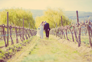 Heather and Matt kiss in the vineyard at Cave B/Sagecliffe