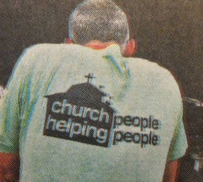 Back of a man wearing a t-shirt that has a black church shape on it with the words Church Helping inside it and then the words People People to the right