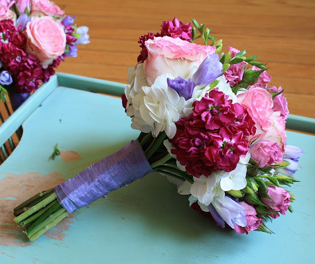 Bridesmaids bouquets fuchsia stock, lavender freesia, pink Esperanza roses, and mauve spray roses - Splendid Stems Floral Designs