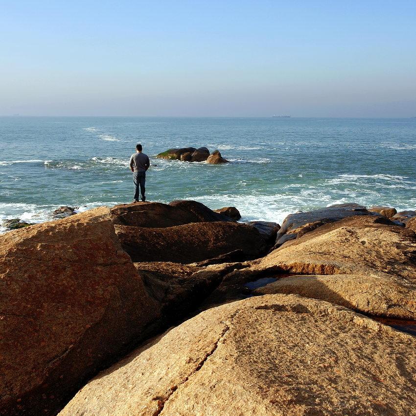 Zona rochosa à beira mar e um homem de costas a olhar a zona de rebentação das ondas. Céu limpo