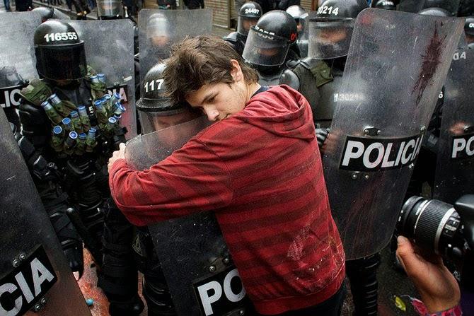 Студент обнимает штурмовика во время протестов против образовательной реформы в Боготе, Колумбия, 2011 год.