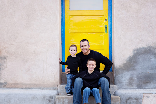 Father and sons sit on steps with a Brilliant colored background