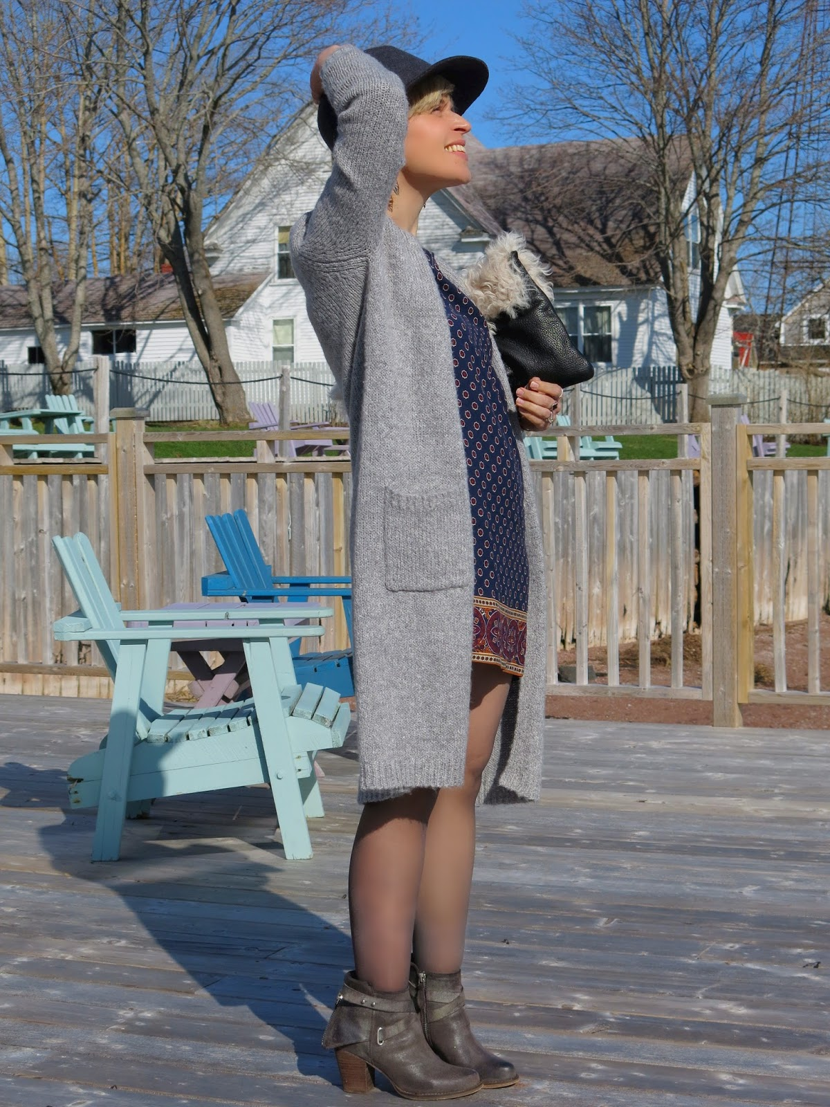 styling a printed mini-dress with a long cardigan, booties and a floppy hat