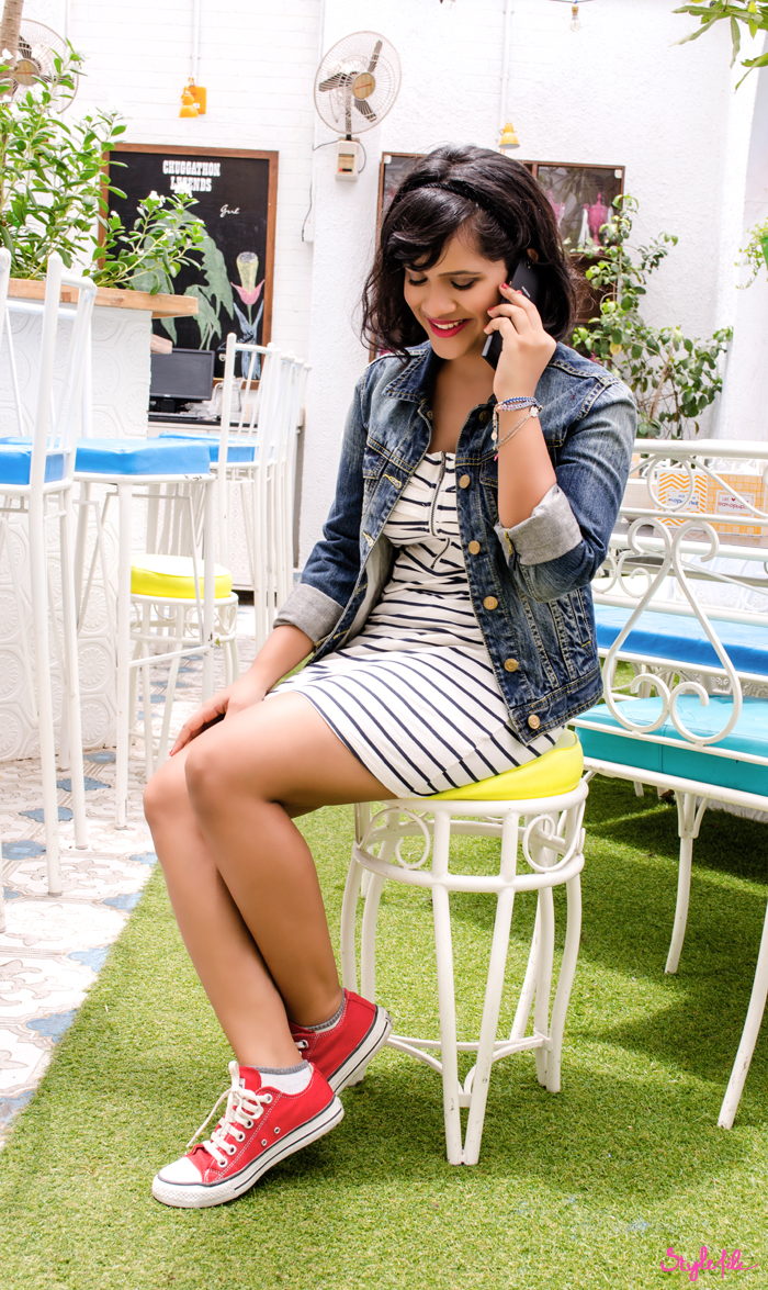 Dayle Pereira of the blog Style File takes a call on the Phicomm Passion 660 while wearing a striped tube dress, denim jacket and red converse sneakers