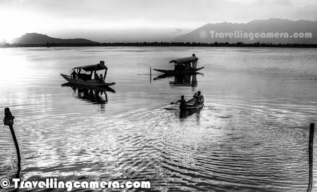 Dal Lake is beautiful lake in Srinagar city of Jammu & Kashmir State. Shrinagar is also know as summer capital of Jammu and Kashmir State of India. The urban lake, which is the second largest in the state, is integral to tourism and recreation in Kashmir and is nicknamed the 'Jewel in the crown of Kashmir' or 'Srinagar's Jewel'. The lake is also an important source for commercial operations in fishing and water plant harvesting. Let's check out this Photo Journey to know more about Dal Lake in this beautiful city of Kashmir !Last month I was in Shrinagar for 3rd Mughal Rally by Himalayan Motorsports and all these photographs are shot during one of the evenings, when we were relatively free and could spend some time around Nagin & Dal Lake. Although one of the mornings we also went for Shikara Ride through Old Kashmir and markets around lake. We shall also be sharing same photographs in colors soon, as sunset colors were really magical...Dal lake is quite popular as a visitor attraction and a summer resort for tourists from various parts of India and other countries. Fisheries and the harvesting of food and fodder plants are also important on Dal Lake. Weeds from the lake are extracted and converted into compost for the gardens. It also serves as a flood lung of the Jhelum River. Swimming, boating, snow skiing and canoeing are amongst some of the water sports activities practiced on the lake.Various Houseboats can be seen around different Lakes in Shrinagar. Houseboats and the Dal Lake are widely associated with Srinigar and are nicknamed 'floating palaces', built according to British customs. The houseboats are generally made from local cedar-wood and are graded in a similar fashion to hotels according to level of comfort. Many of them have lavishly furnished rooms, with verandas and a terrace to serve as a sun-deck or to serve evening cocktails. They are mainly moored along the western periphery of the lake, close to the lakeside boulevard in the vicinity of the Dal gate and on small islands in the lake. They are anchored individually, with interconnecting bridges providing access from one boat to the other. The kitchen-boat is annexed to the main houseboat, which also serves as residence of the boat-keeper and his family(Courtesy - http://en.wikipedia.org/wiki/Dal_Lake)Dal Lake is in the heart of Srinagar city and is well connected by road & air links. The nearest airport, which connects with other major cities in the country, is about 7 kilometres away at Badgam. The nearest railway station is 300 kilometres away at Jammu. The National Highway NH1A connects the Kashmir valley with rest of the countrDal lake covers an area of around 18 square kilometres and is part of a natural wetland which covers around 21 square kms, including its floating gardens. The floating gardens, known as 'Rad' in Kashmiri, blossom with lotus flowers during July and AugustThe wetland is divided by causeways into four basins - Gagribal, Lokut Dal, Bod Dal and Nagin. Nagin is also considered as separate lake and we stayed Centaur Hotel which is near to Nagin Lake only. Lokut-dal and Bod-dal each have an island in the centre, known as Rup Lank  and Sona Lank respectively.Shoreline of the Dal Lake is about 15.5 kilometres and encompassed by a boulevard lined with Mughal era gardens, parks, houseboats and hotels. Scenic views of Dal lake can be witnessed from Mughal gardens, such as Shalimar Bagh and Nishat Bagh built during the reign of Mughal Emperor Jahangir and from houseboats cruising along the lake in the colourful shikaras.Dal lake has numerous sites and places of interest, many of which are important to the cultural heritage of Srinigar. Aside from the Shalimar Bagh and Nishat Bagh, some of the other places frequented by tourists are the Shankaracharya temple, the Hari Parbat, the Nagin Lake, the Chashme Shahi, the Hazratbal Shrine, the famous Kashmir houseboats and the Shikara (boat) called the Gandola of Kashmir.Shikaras provide a water taxi service available to see the sights in the Dal Lake and to approach the houseboats moored on the lake periphery.Dal Lake has become an icon of the Kashmir tourism industry and almost every tourist dream of having a Shikara ride in this lake and stay at least for one night in House-Boats. A Himalayan urban lake which has five basins and a number of channels that are well linked with each other. There are plenty of fishes in Dal Lake and fishery is the second largest industry of the region centered on the lake.The sparkling quiet waters of Dal surrounded by snow-capped mountains on its three sides, undoubtedly mark it as one of the most beautiful lakes of India. It is also the second largest lake in the State of Jammu and Kashmir with numerous gardens and orchards all along its shores. Houseboats form an indelible part of the scenery of the Dal Lake that are always ready to take tourists to a romantic and peaceful ride of the lake and soothe their nerves as the houseboat floats over the slightly rippling waters. They also offer some of the most exotic views of the splendid scenery of the Dal Lake.
