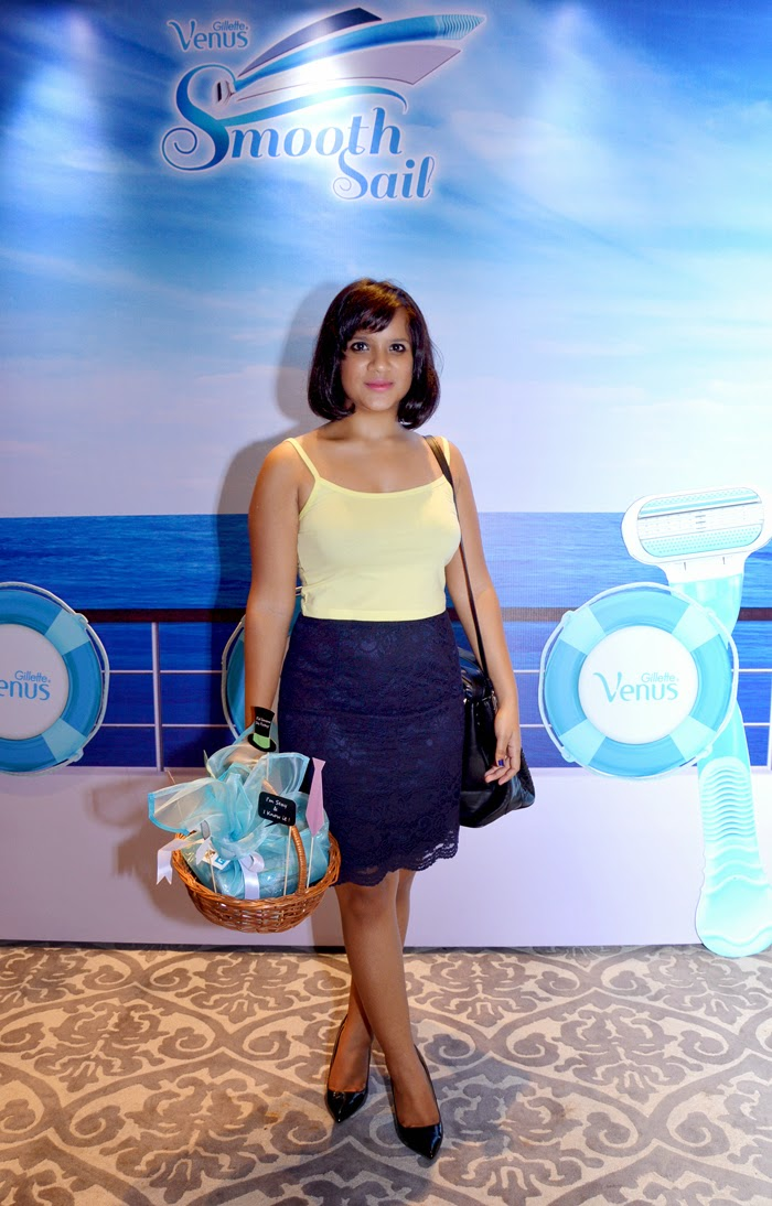 Dayle Pereira of Style File India with a staright bob hairstyle wears a yellow crop top and blue lace pencil skirt with pumps and a handbag as she posses in front of the Gillette Venus press board with a goodie basket and photo props in her hand