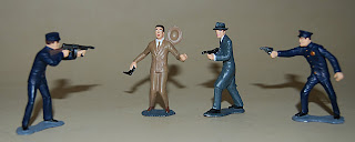 Toys, lead figurines of police officers holding pistol and Tommy gun, man in beige holding pistol, man in gray holding Tommy gun, unknown date. 2006.423.1-4. Collection of the NLEM, Washington, DC.