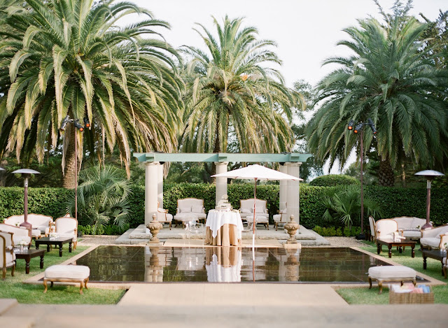lounge area at a Montecito spring wedding reception with upholstered Louis armchairs and setteesdesigned by Yifat Oren