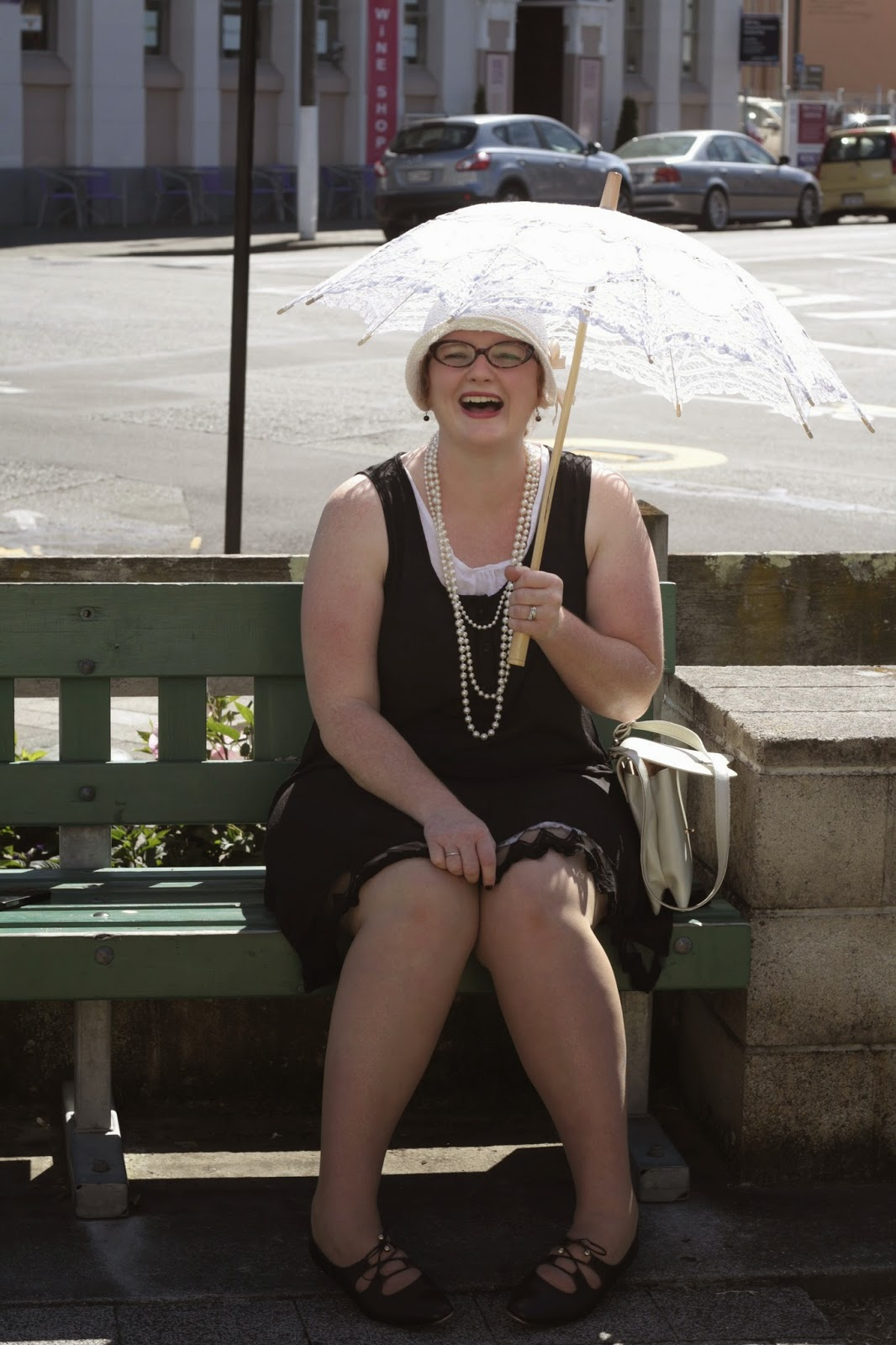 Jenn has an art deco dress, lots of pearls, a smile and a parasol.