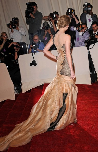 Taylor Swift in a gunmetal and peach, one-shoulder gown.