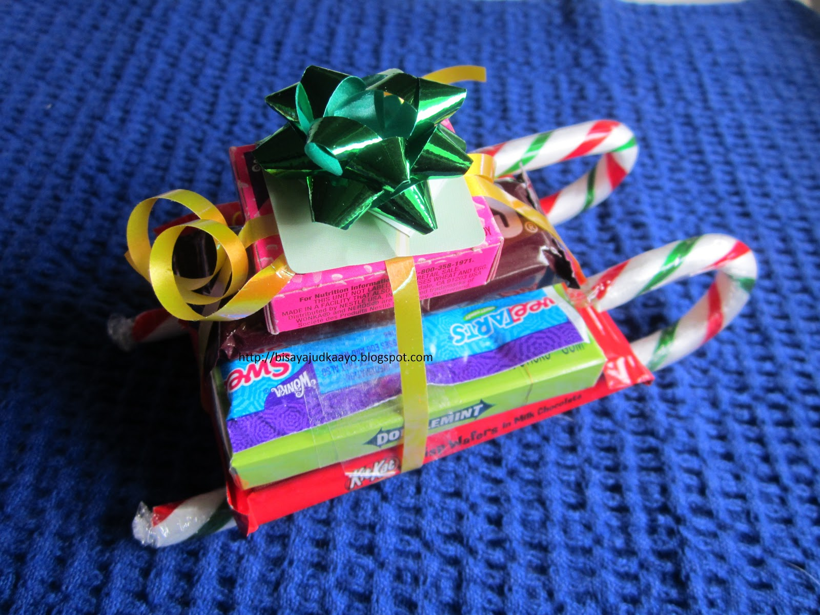 start stacking your candies i taped each candies making sure they are sturdy then top with mini ribbons or embellish with more ribbons if you want - Christmas Candy Sleigh