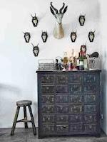 Komoda w skandynawskim stylu, drewniany taboret i poroża na ścianie