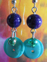 Long drop earrings have teal fashion buttons and small beads hanging from purple river stones