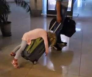 Young girl lying face-first over a rolling suitcase being pulled by her father
