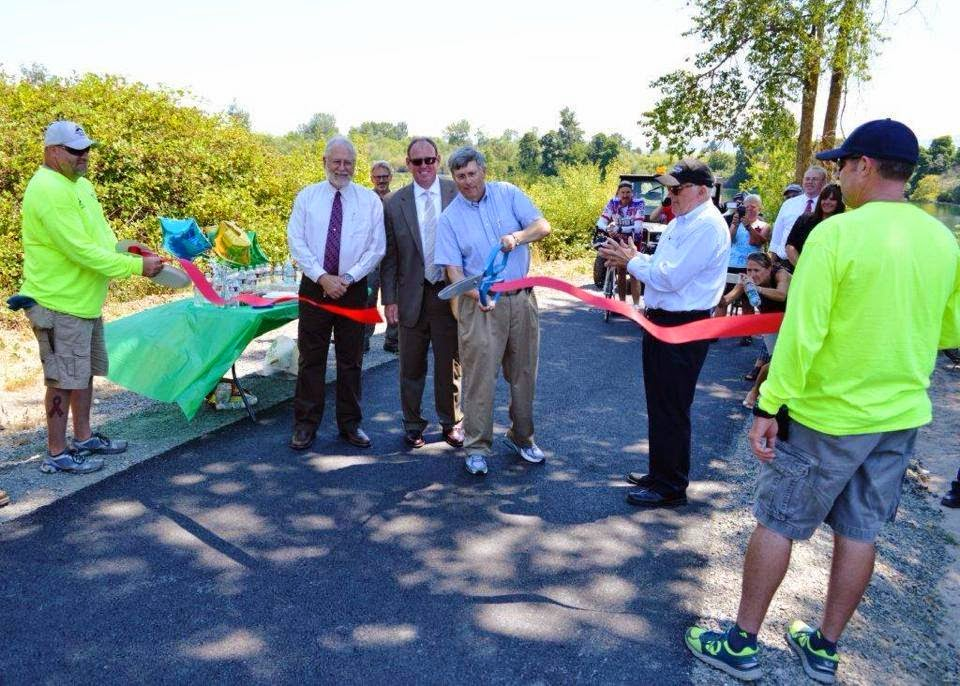 Using a giant pair of scissors, a man in slacks and short-sleeved button-up shirt cuts a red ribbon that is stretched at waist-height across a segment of paved trail. Behind him, other men, wearing slacks, dress shirts, and ties, look on. Two men in shorts and long-sleeved T-shirts hold the ribbon-ends.