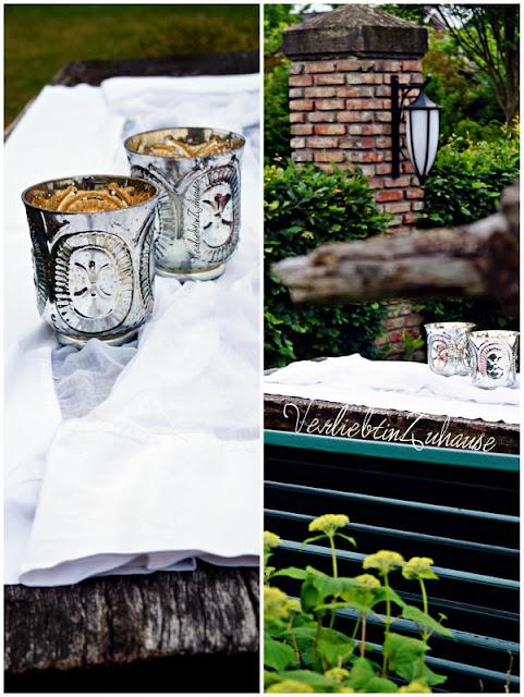 Windlicht, Teelichthalter aus Glas mit Bauernsilber. Im Garten hübsch dekoriert auf rustikalem Holztisch
