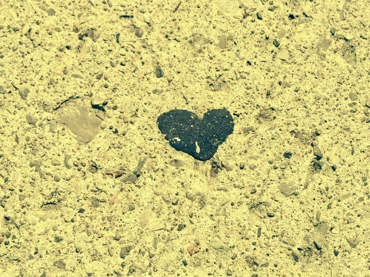 little black heart on city sidewalk