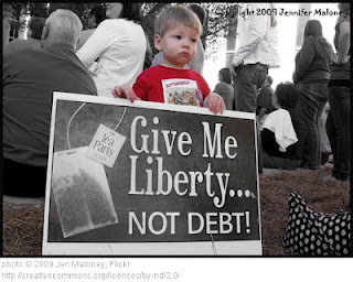 "child holding sign: ""Give me liberty, not debt!"""