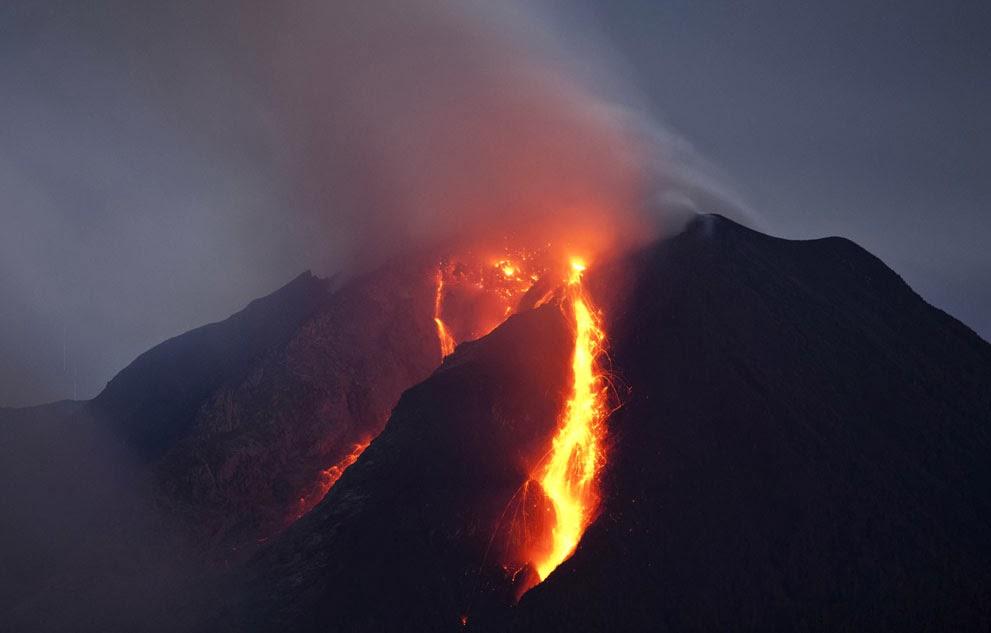 Lava pijar mengalir turun dari kubah lava Gunung Sinabung, di Kabupaten Karo, Sumatera Utara,