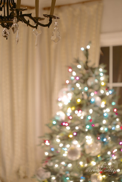 Christmas bedroom chandelier and colorful tree in background